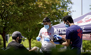 3 people outside wearing masks and gloves, distributing equipment